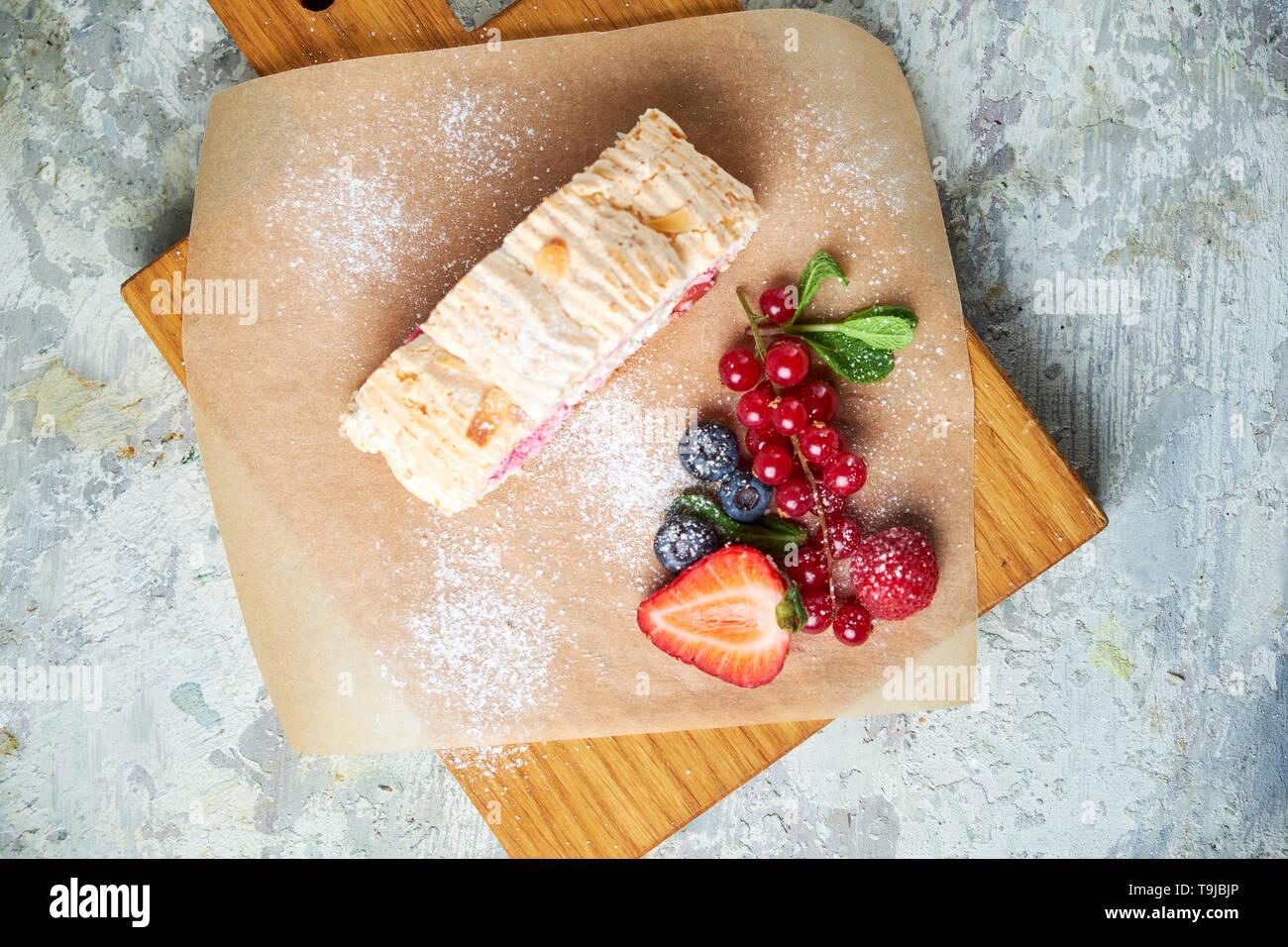 Rouleau de meringue est décoré avec des baies sur une planche de bois. Vue de dessus.fond texturé gris. Beaux plats de service. Le Dessert. La chaîne alimentaire Banque D'Images