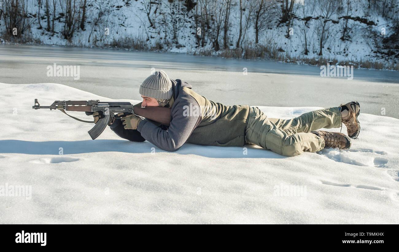 La démonstration de l'instructeur de combat la position du corps à la carabine à l'hiver la neige profonde. Lutte contre l'avancée des cours de tir tactique de tir sur ran Photo Stock