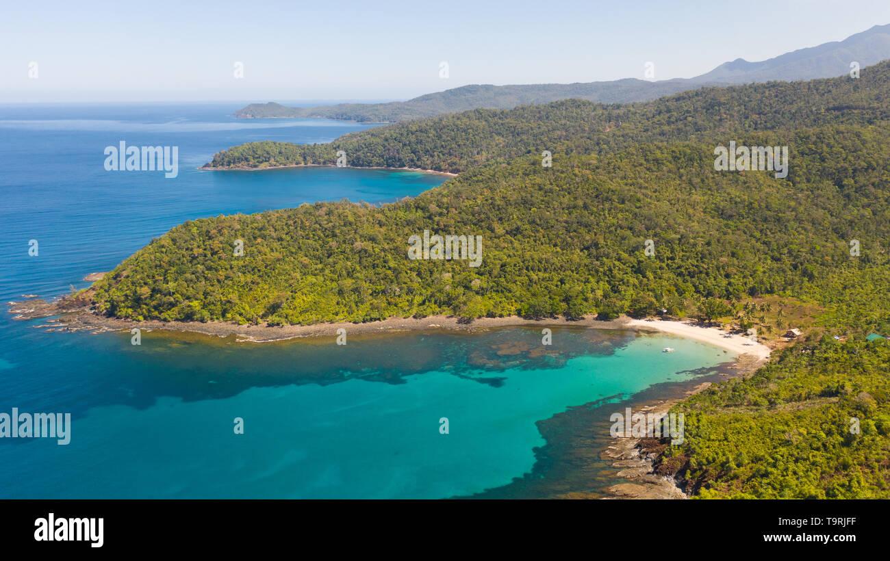 Mer baie aux eaux turquoises et d'une petite plage de sable blanc.Côte de l'île de Camiguin, Philippines.magnifique lagon et l'île volcanique couverte de forêts denses, vue de dessus. Banque D'Images