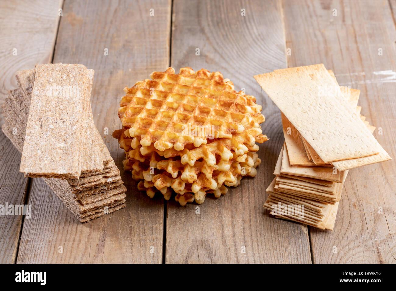 Sweet tour de gaufres et de calories grain sain crispbreads sur de vieilles tables en bois. Des collations saines et malsaines. Photo Stock