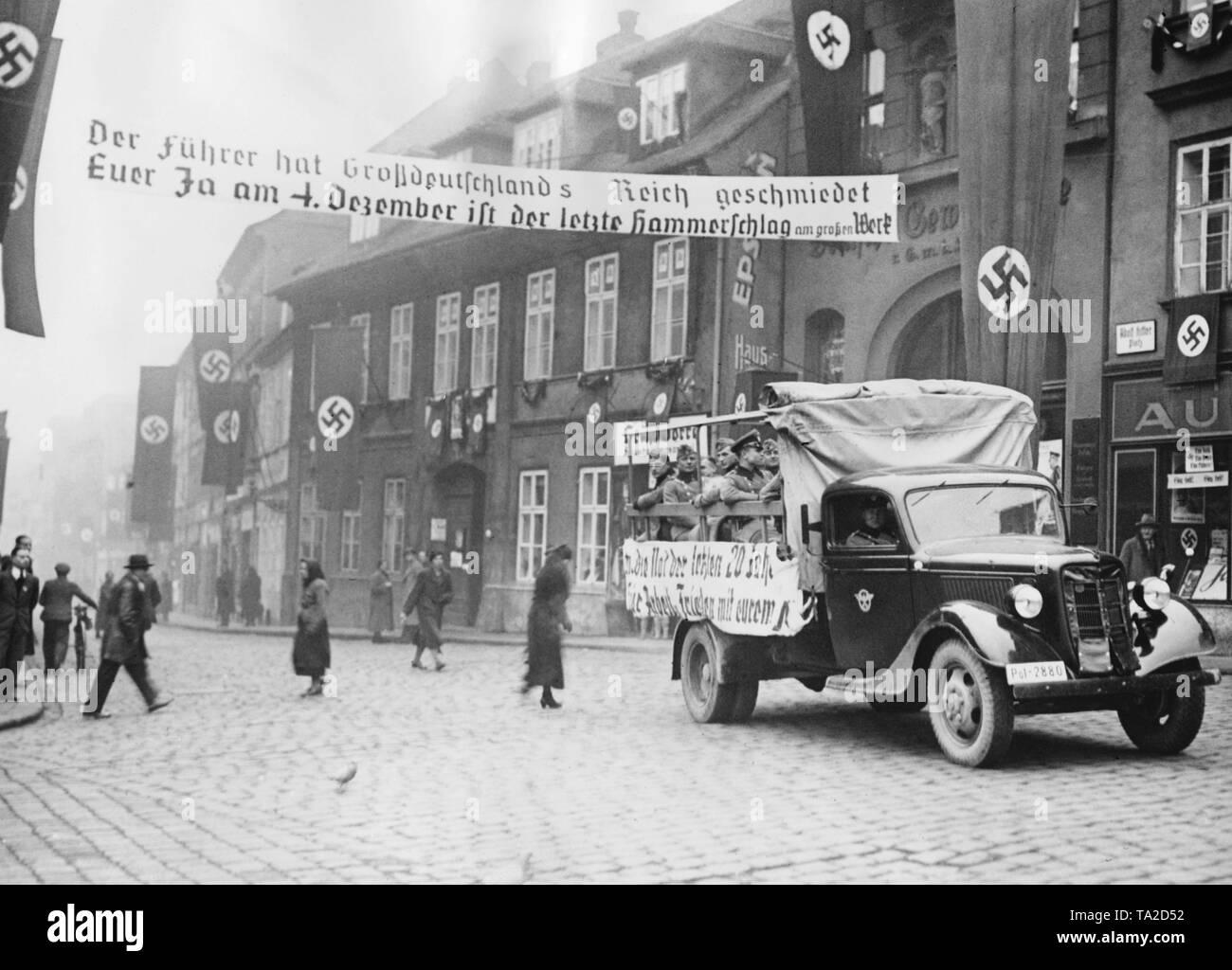 """Voiture de l'Ordnungspolizei (police régulières de l'Allemagne nazie) avec porte à Tellnitz Telnice (aujourd'hui). La ville est décorée avec des drapeaux à croix gammée. Les Allemands de Sudeten tenir une élection partielle en ce qui concerne l'annexion des Sudètes au Reich allemand. Sur l'affiche sur la rue: """"Le führer a forgé le grand Empire Allemand / Votre Oui le 4 décembre est le dernier coup de marteau sur l'excellent travail"""". Photo Stock"""
