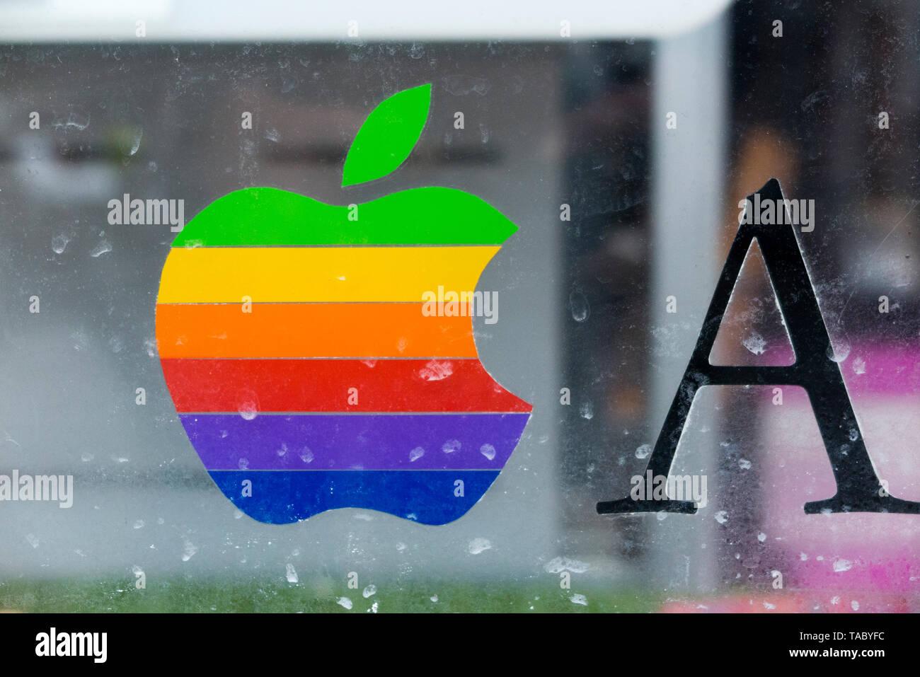 Arc-en-ciel classique mordu ordinateurs Apple logo autocollant de fenêtre dans un ordinateur réparation / fenêtre / réparateurs shop Revendeur Apple, au Royaume-Uni. (99) Photo Stock