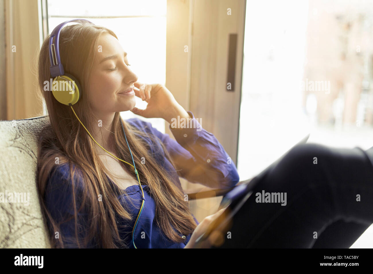 Ambiance jeune femme assise sur une chaise portant des écouteurs Banque D'Images
