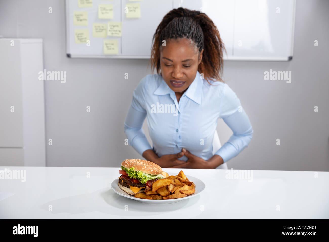 Jeune femme souffrant de douleurs à l'estomac pendant le petit-déjeuner Banque D'Images