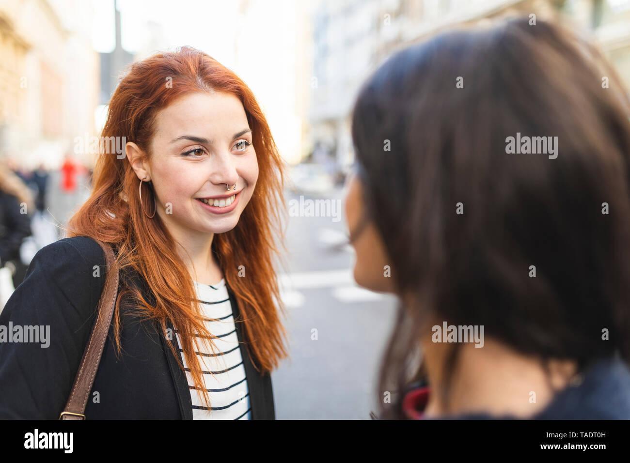 Portrait de jeune femme rousse de piercing avec passer du temps avec son ami dans la ville Banque D'Images