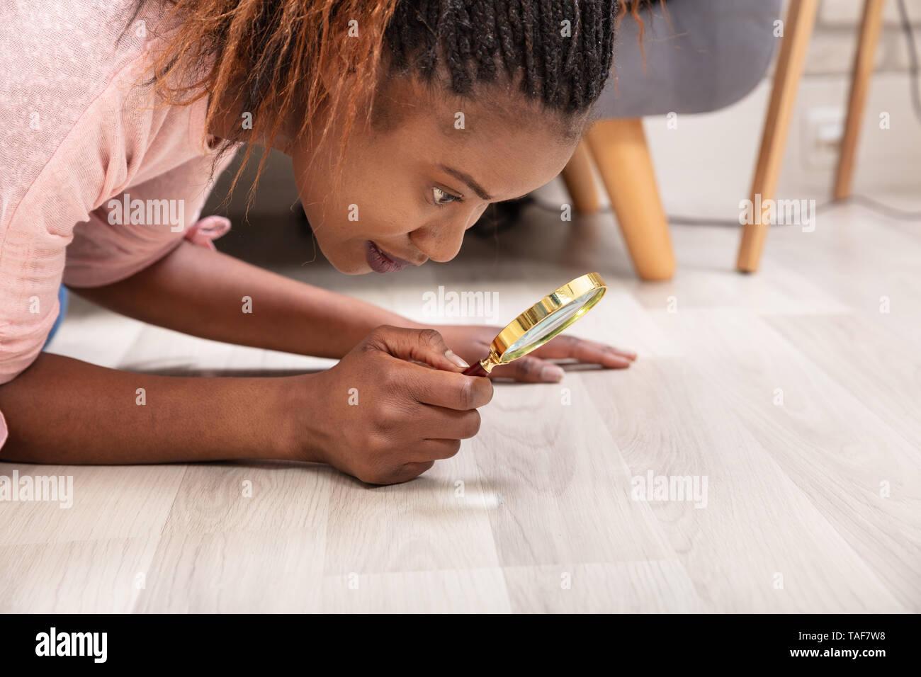 Vue latérale d'une jeune femme à la recherche de plancher de bois franc par Loupe Photo Stock
