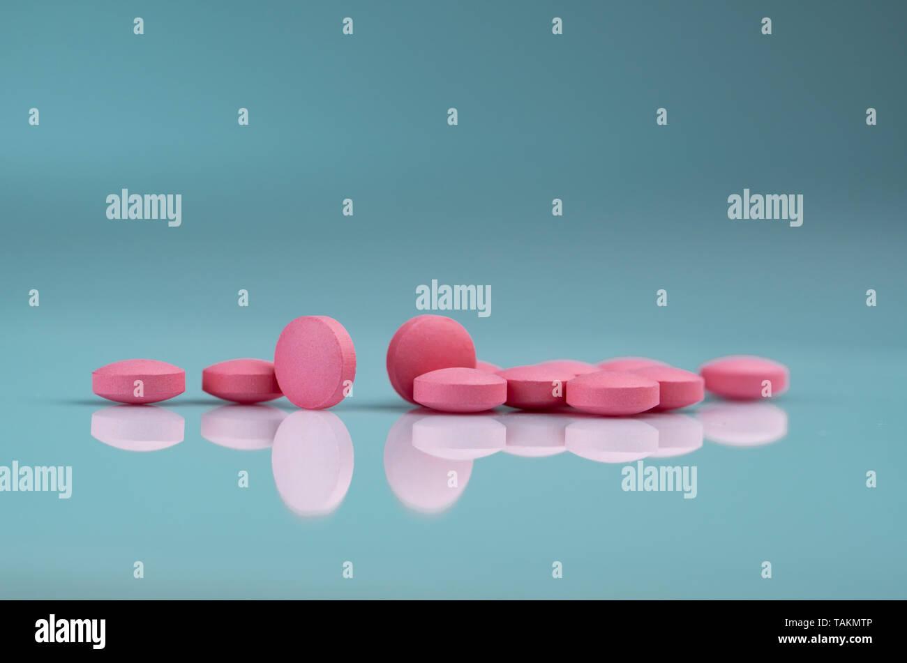 Comprimé rond comprimés roses sur fond dégradé. Vitamines et minéraux et l'acide folique vitamine E et le zinc de la bouteille sur fond dégradé. Pink Photo Stock