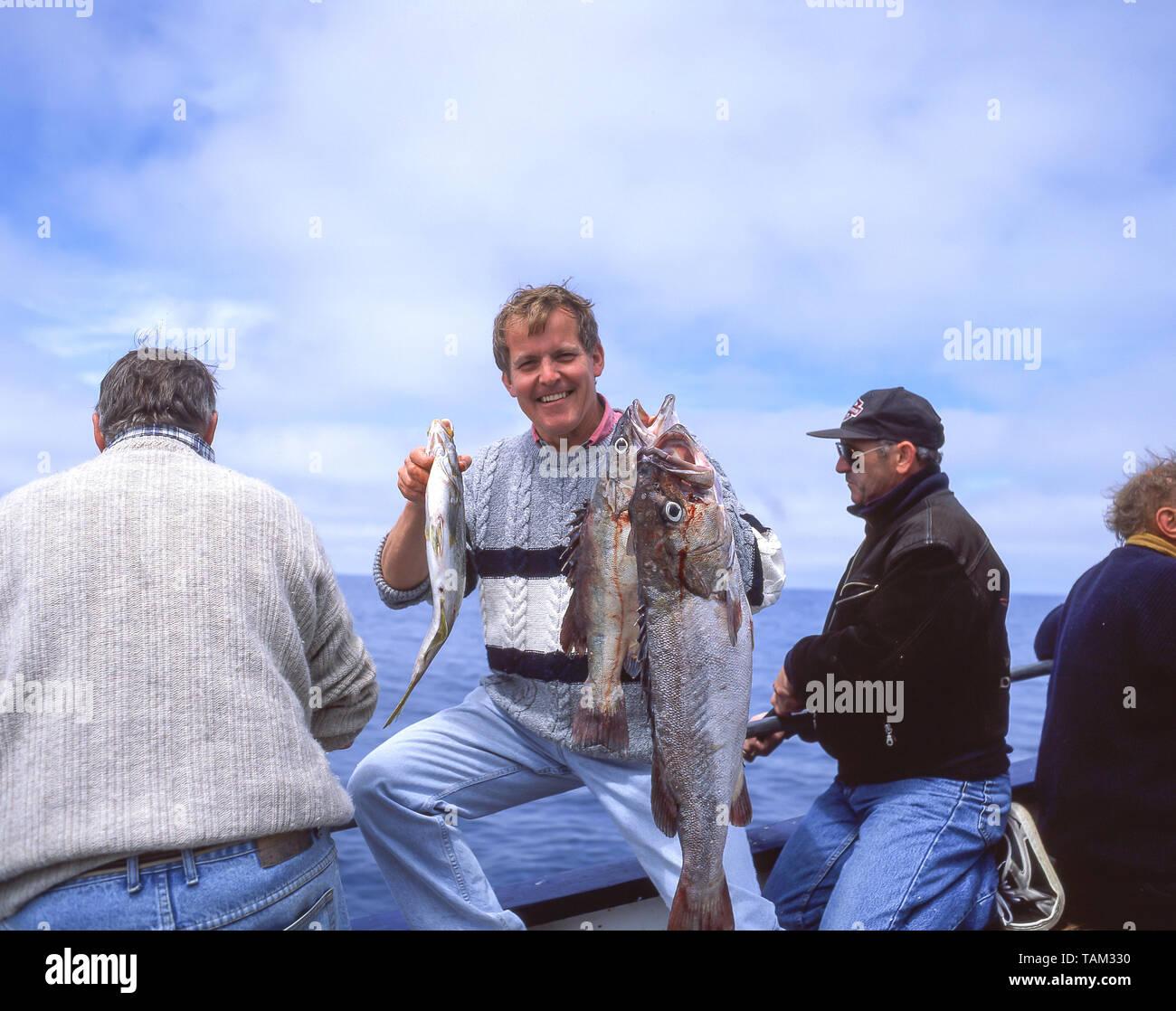 Jeune homme tenant un poisson attraper sur bateau de pêche, Oamaru, Région de l'Otago, île du Sud, Nouvelle-Zélande Banque D'Images