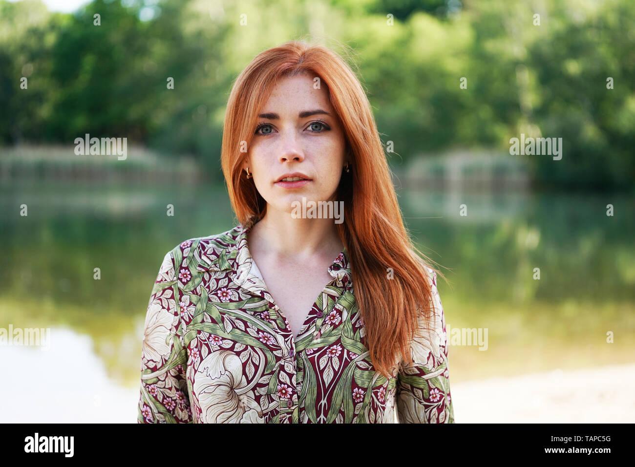 Cool et confiante jeune femme portant robe motif floral avec de longs cheveux rouges par le lac - authentique des personnes réelles Banque D'Images