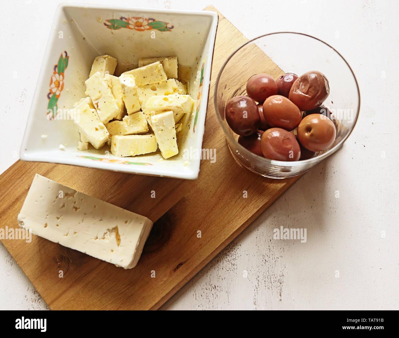 Le fromage Feta habillé avec le poivre et l'huile d'olive et olives noires grecques Banque D'Images
