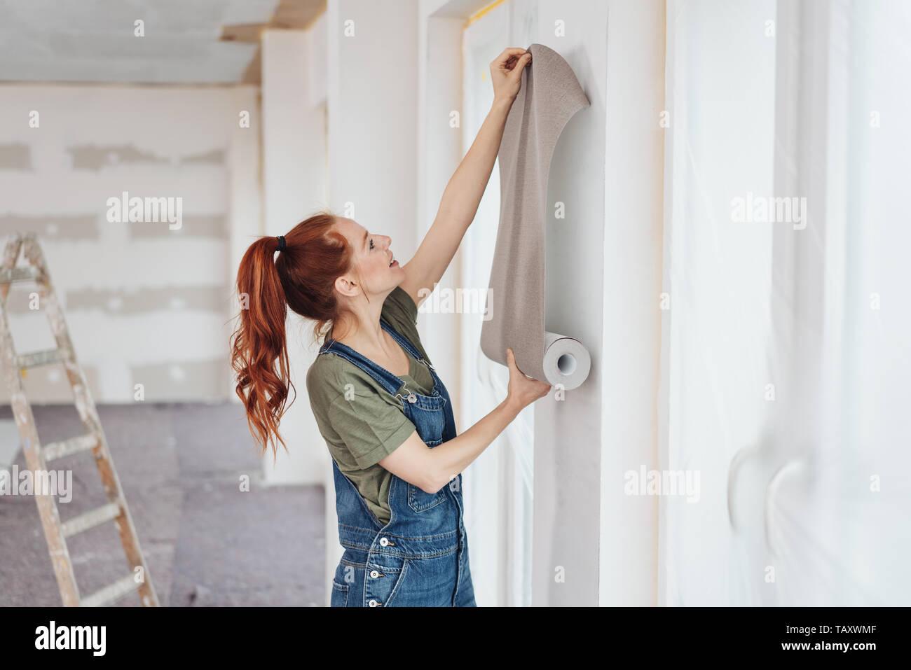 Jeune femme essayant de nouveaux fond d'écran à la maison maintenant la contre un mur blanc nouvellement peintes pour l'effet visuel Photo Stock