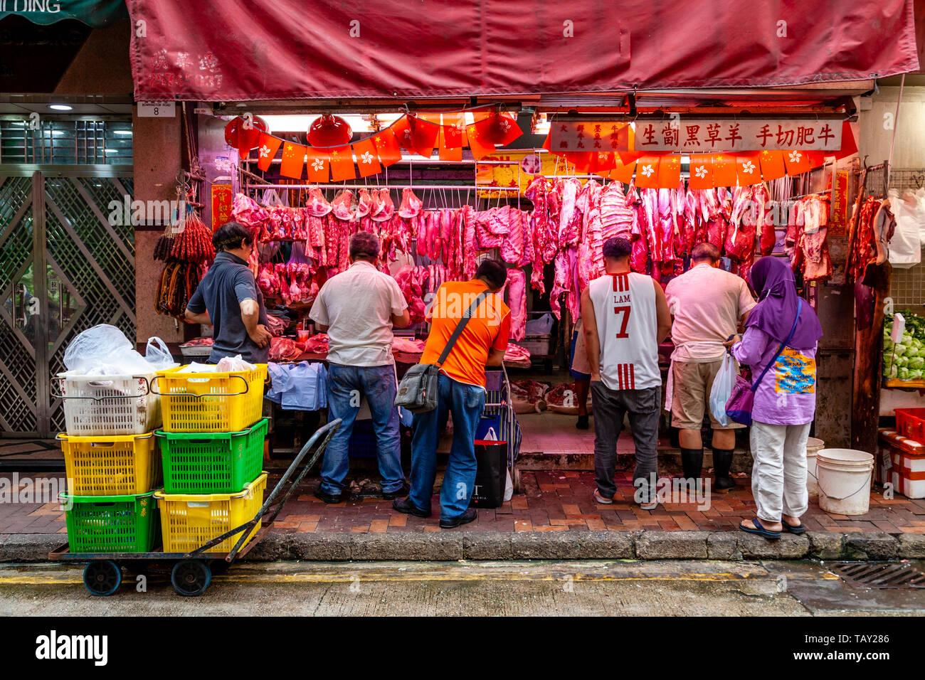 Les gens d'acheter de la viande à un magasin à la boucherie Bowrington Road Food Market, Hong Kong, Chine Banque D'Images