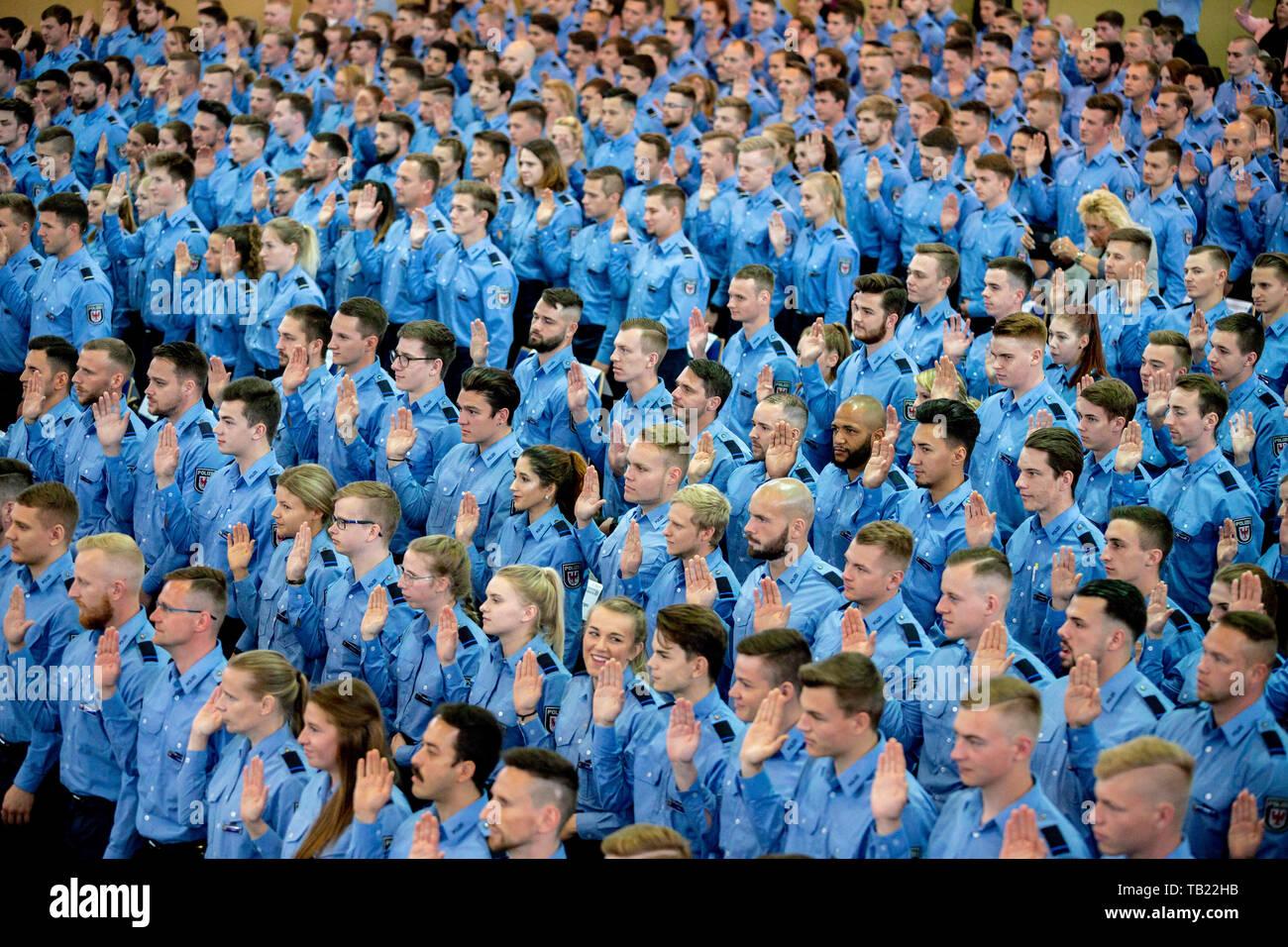 Oranienburg, Allemagne. 29 mai, 2019. Les futurs agents de police lever leur main droite au cours de la cérémonie d'assermentation des 2018 année de recrutement à l'Université de Sciences Appliquées de Oranienburg. Près de 400 policiers sont assermentés. Credit: Christoph Soeder/dpa/Alamy Live News Photo Stock