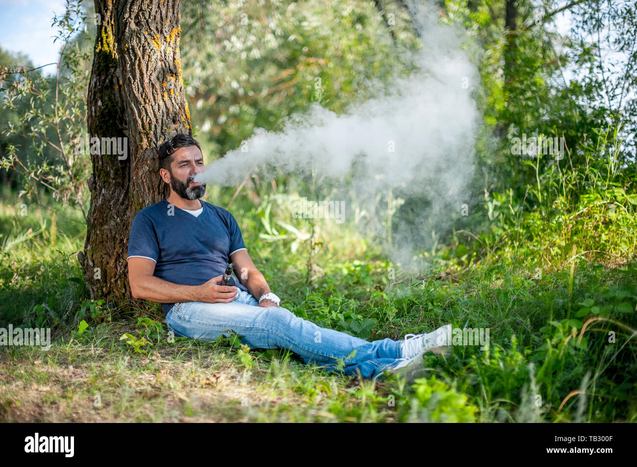 Beardedman élégant explose un couple un vape. Cigarette électronique concept. Banque D'Images