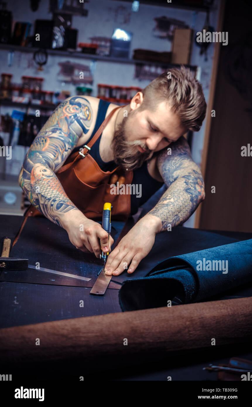 Travailleur du cuir professionnel découpe de cuir à sa zone de travail. Banque D'Images