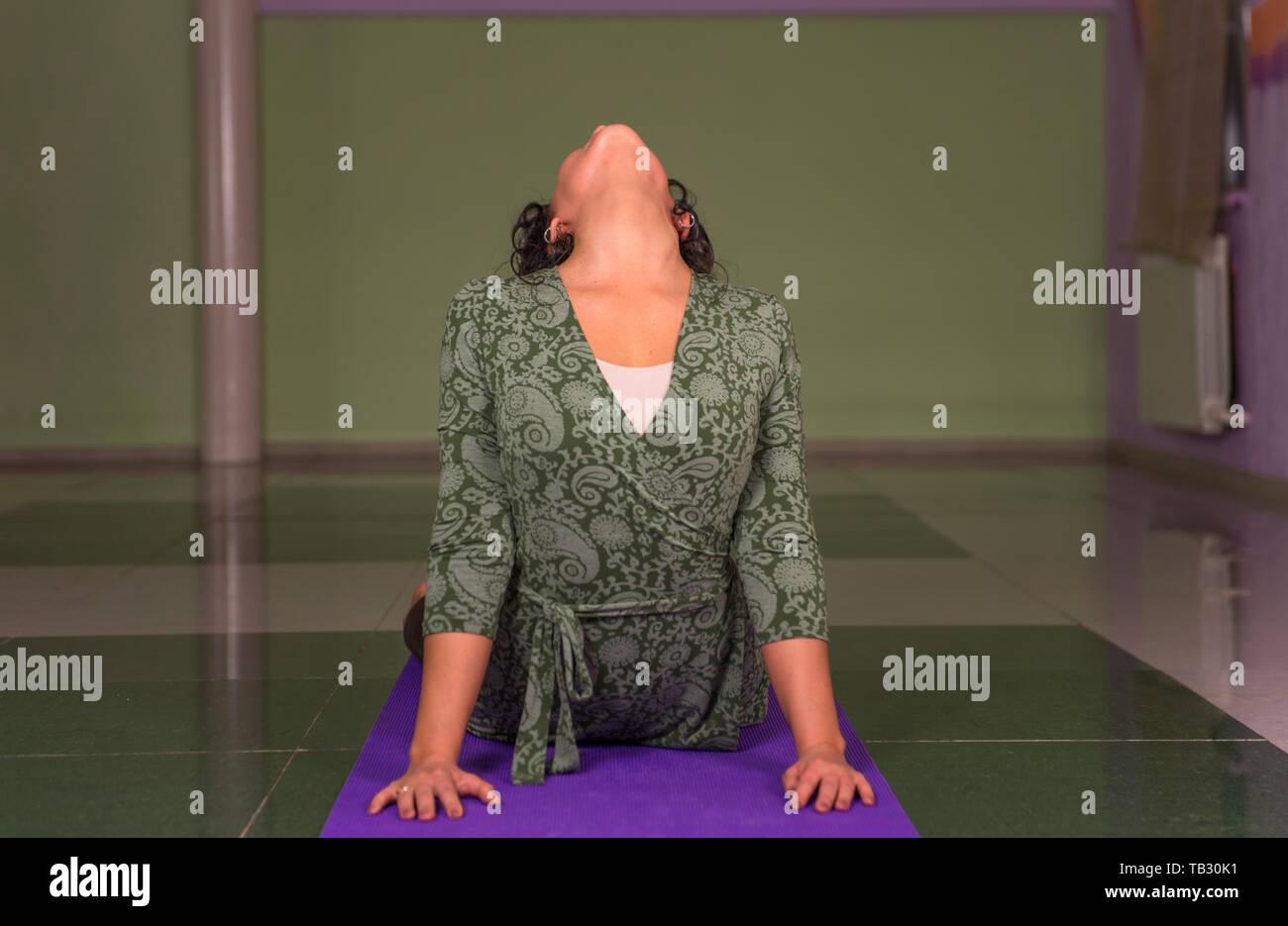 Yoga girl working out en l'étirant dans le yoga dans la salle de sport Banque D'Images