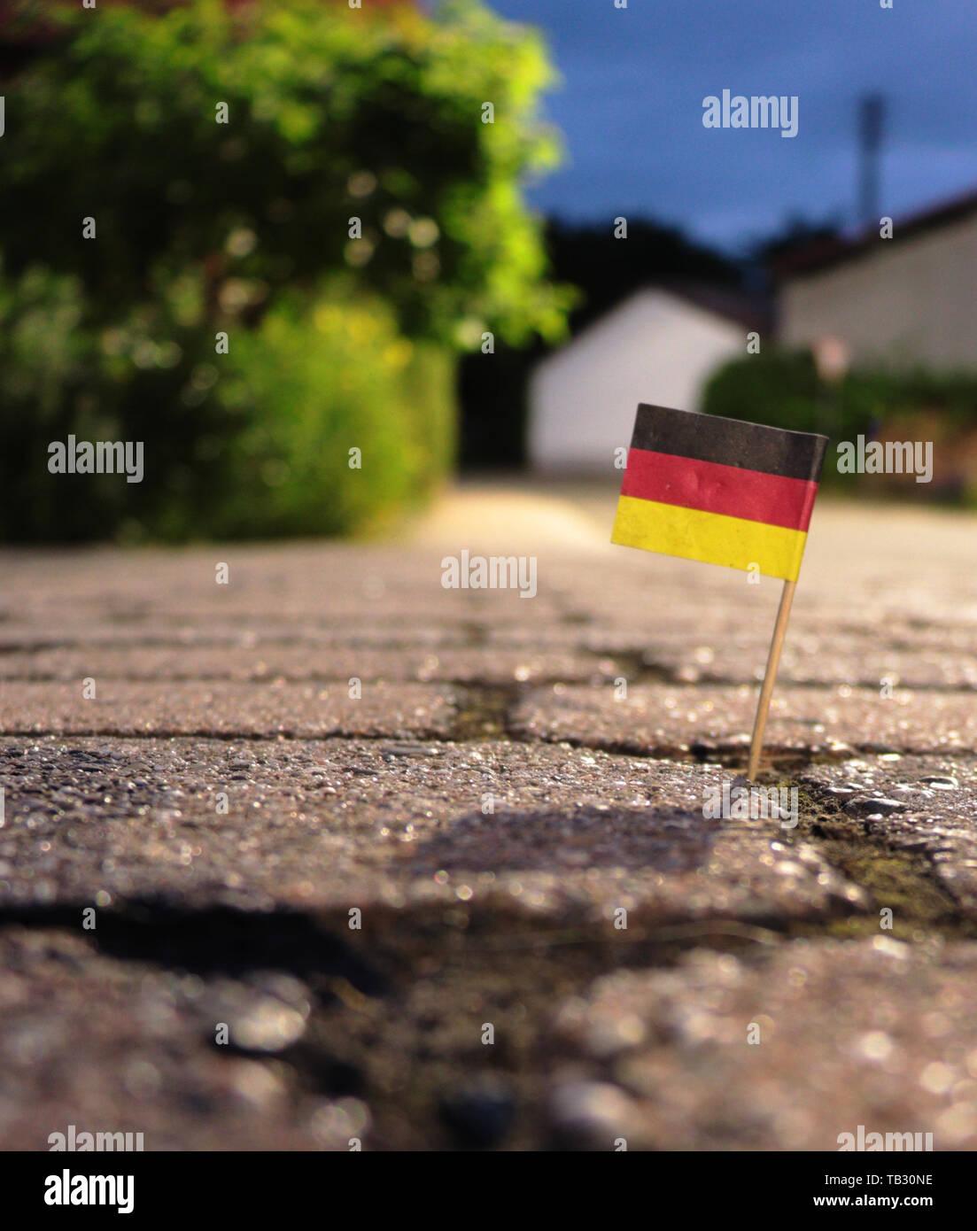 Un cure-dent allemand drapeau est bloqué dans le trottoir craquent après une nuit de fête et de célébration. Photo Stock