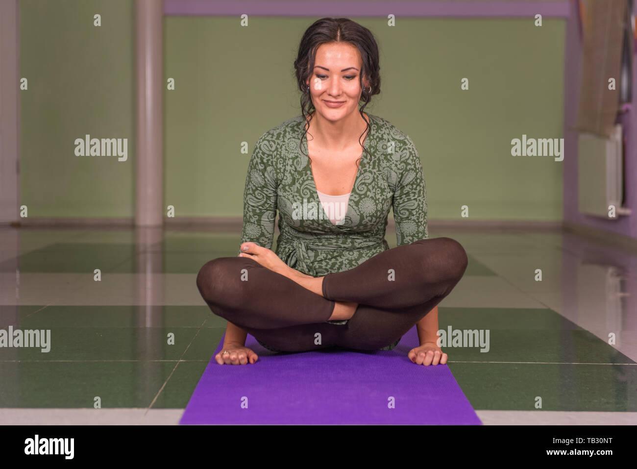 Formateur de yoga professionnel posant dans le yoga en classe de conditionnement physique Banque D'Images