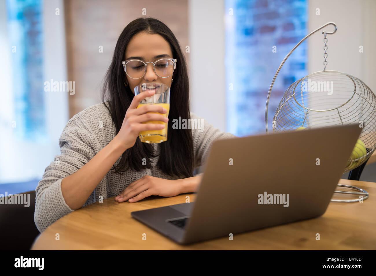 Portrait of Beautiful woman using laptop at table in cuisine intérieur pendant le petit-déjeuner à la maison Banque D'Images