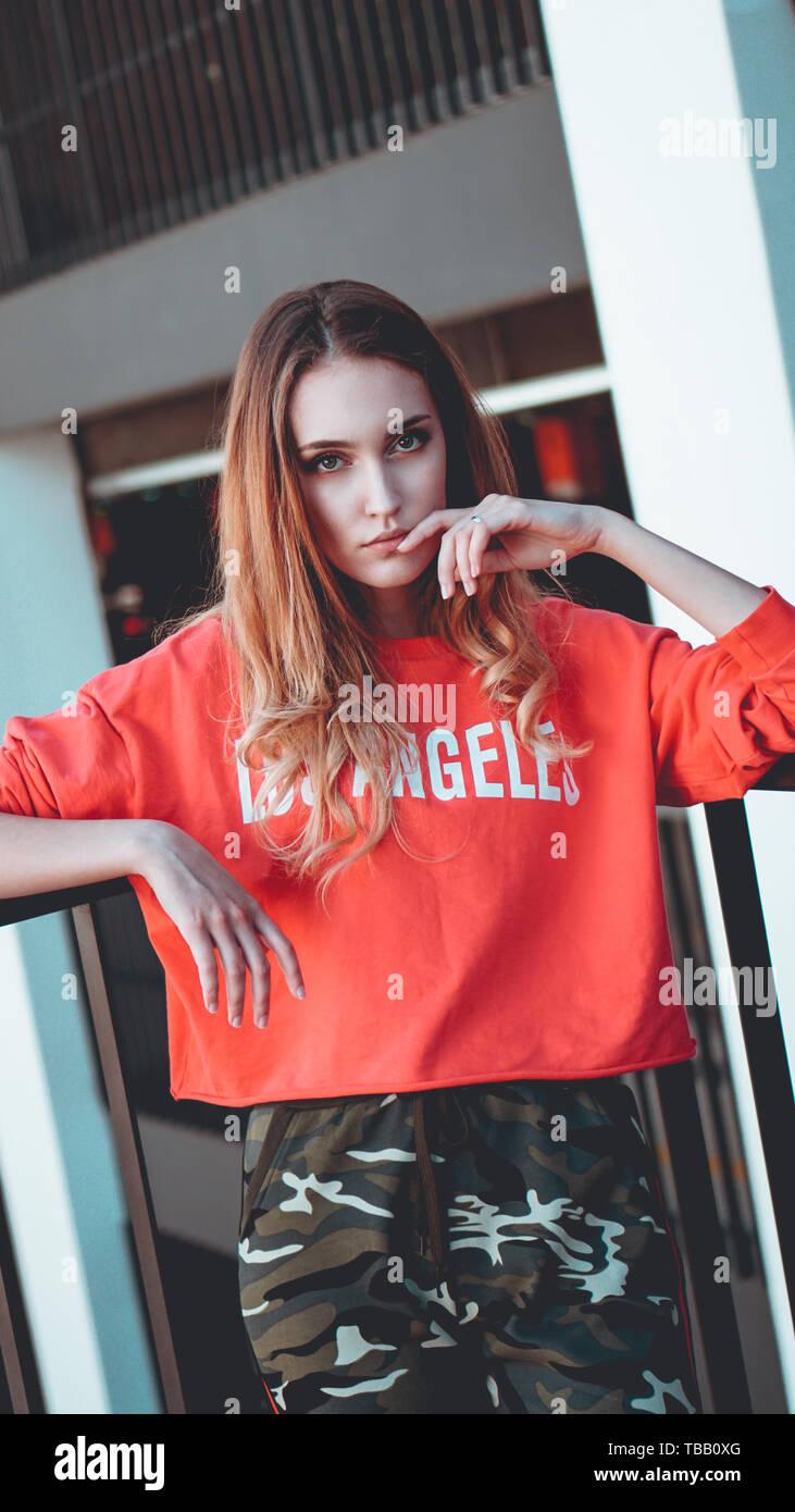 Fashion model wearing red sweat avec l'inscription los angeles posant dans la ville à un parking gratuit. Urban Fashion tenue. Style décontracté de vêtements de tous les jours Photo Stock