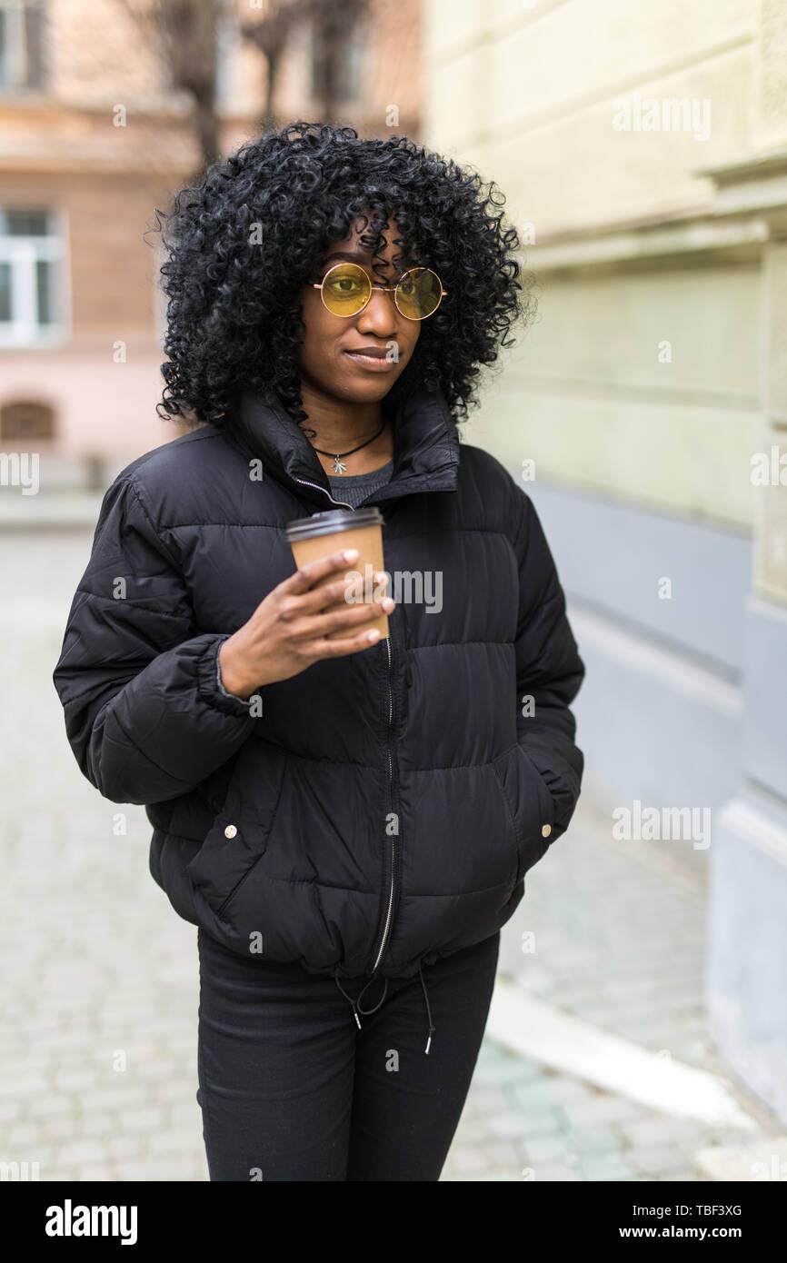 Cheerful young African woman wearing coat la marche à l'extérieur, tenant la tasse de café à emporter Banque D'Images