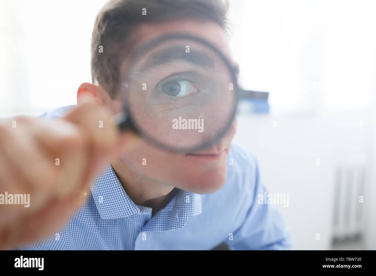 L'homme dans le travail de bureau holding magnifying glass in hand Photo Stock