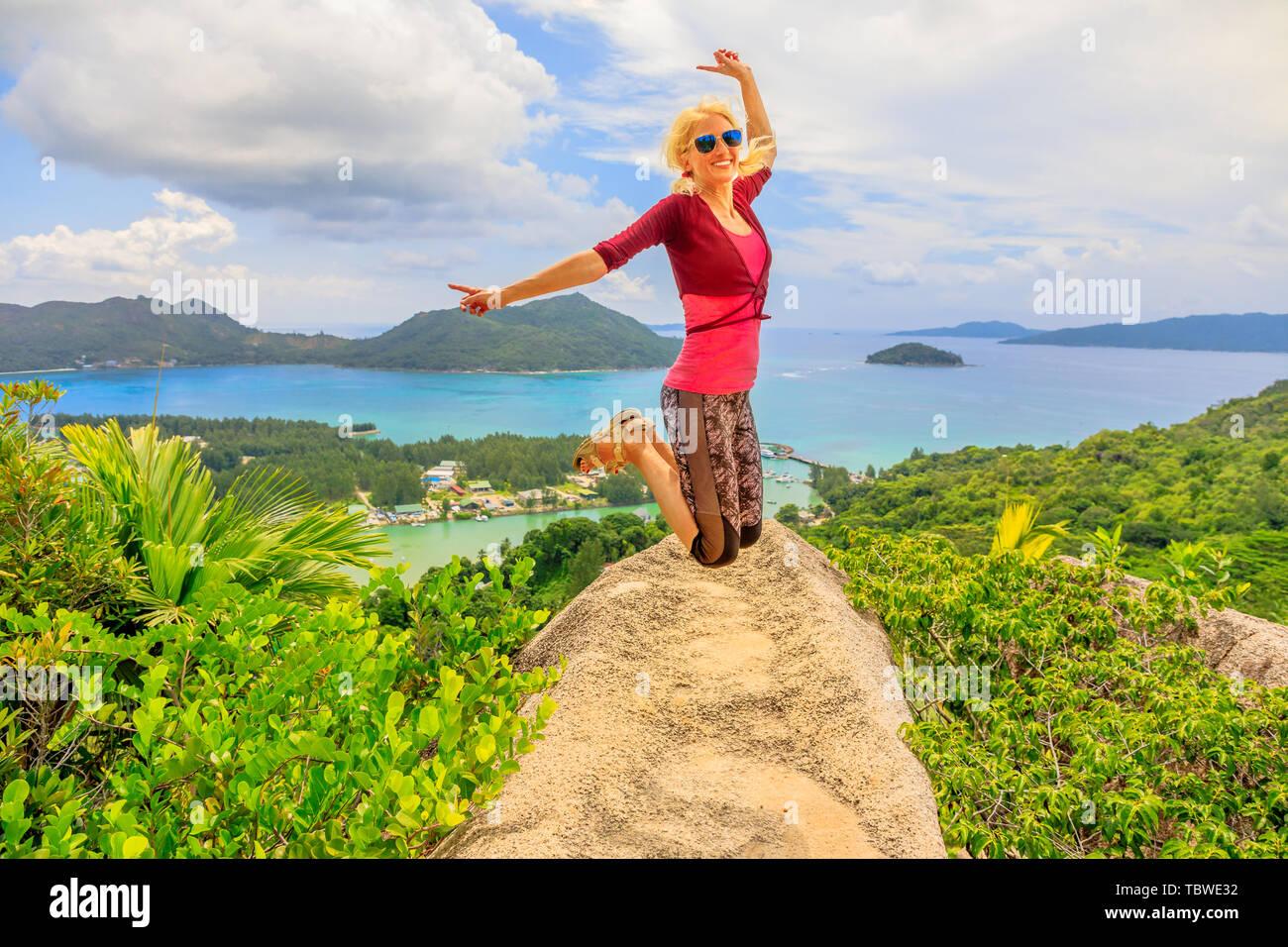 Praslin, Seychelles liberté femme sautant. Heureux joyeux cavalier touristiques à l'île de lookout après une randonnée à l'intérieur de la réserve de fond Ferdinand. Scenic top Photo Stock