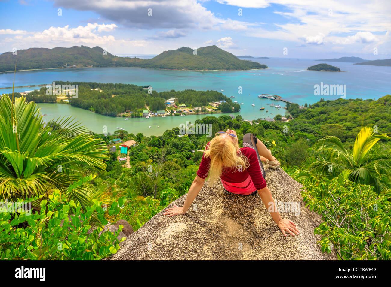 Femme de tourisme détente à lookout de Praslin après la randonnée à l'intérieur de la réserve de fond Ferdinand. Vue panoramique vue de dessus de Praslin sur la baie de Sainte-Anne Photo Stock