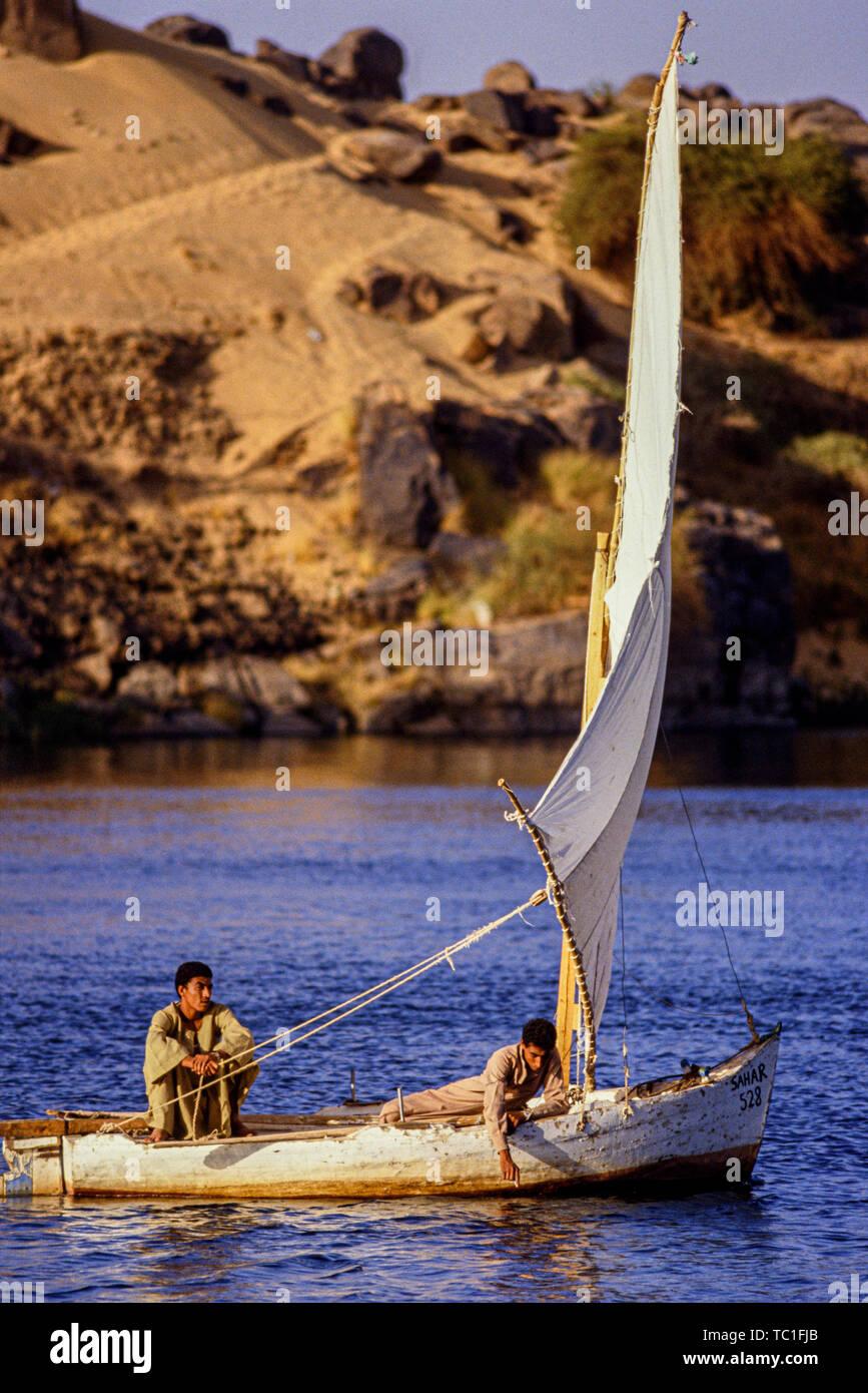 Louxor, Egypte. Deux garçons leur petite voile voilier felouque sur le Nil. Photo: © Simon Grosset. Archive: image numérisé à partir d'un original transpa Banque D'Images