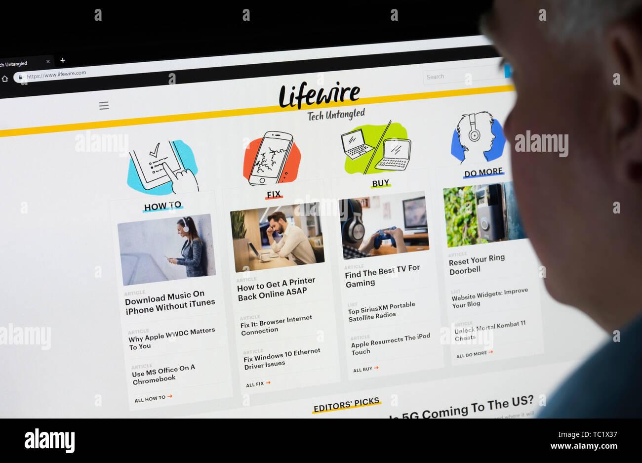 L'homme assis à l'écran d'un ordinateur la navigation au travers de l'Internet à la recherche à l'Lifewire site sur le World Wide Web à l'aide d'un navigateur Internet. Photo Stock