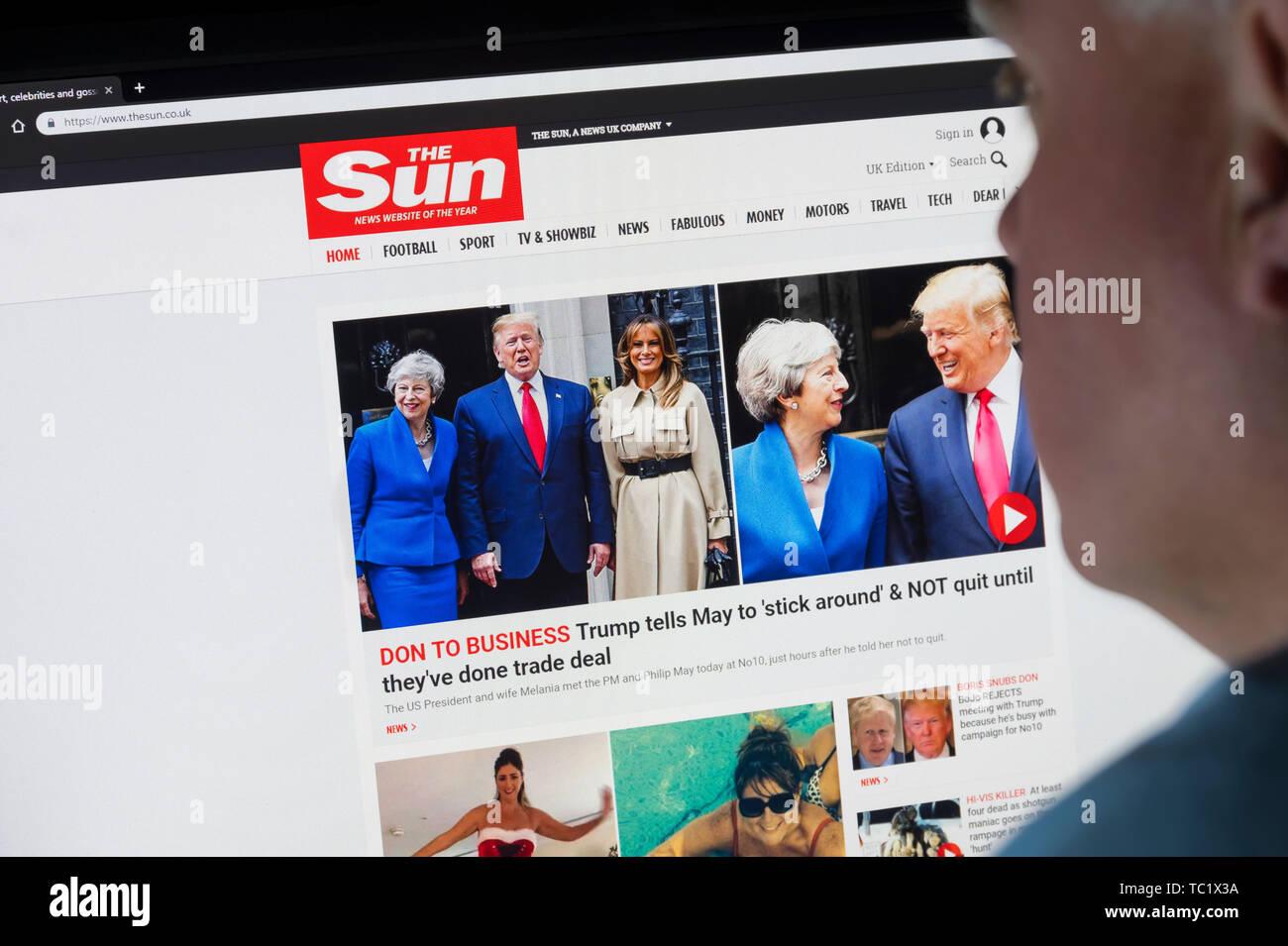 L'homme assis à un écran d'ordinateur, la navigation sur Internet à la recherche sur le site web du journal Le Soleil sur le World Wide Web à l'aide d'un navigateur Internet. Photo Stock