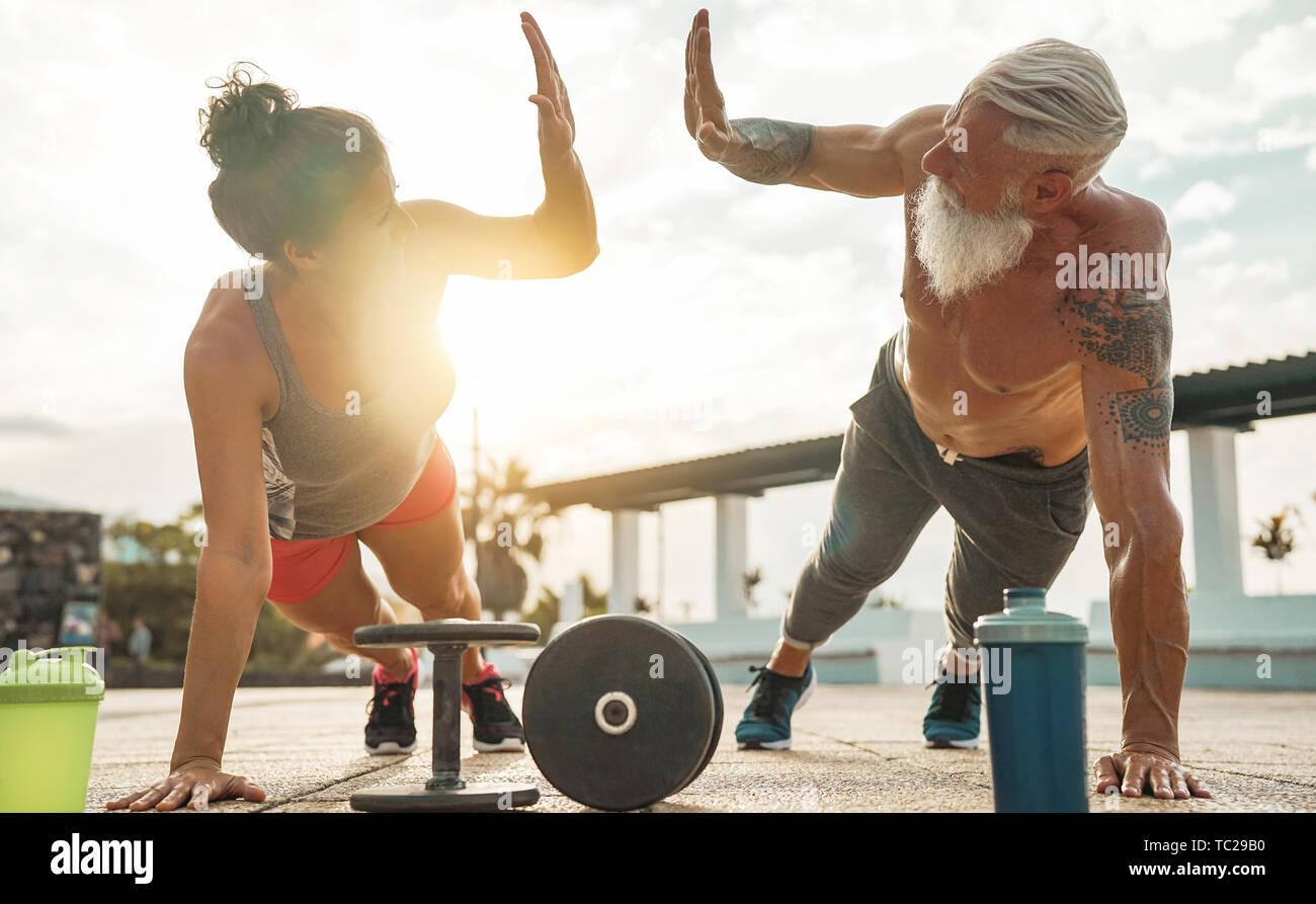 Couple doing Fitness exercice poussez se lève au coucher du soleil en plein air - Heureux les athlètes s séance de gym à l'extérieur de la session Banque D'Images