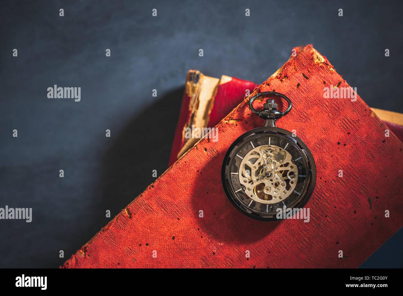 Montre de poche et vieux livre sur plancher de béton. Vue de dessus et copiez l'espace pour le texte. Concept du temps et de l'éducation. Photo Stock