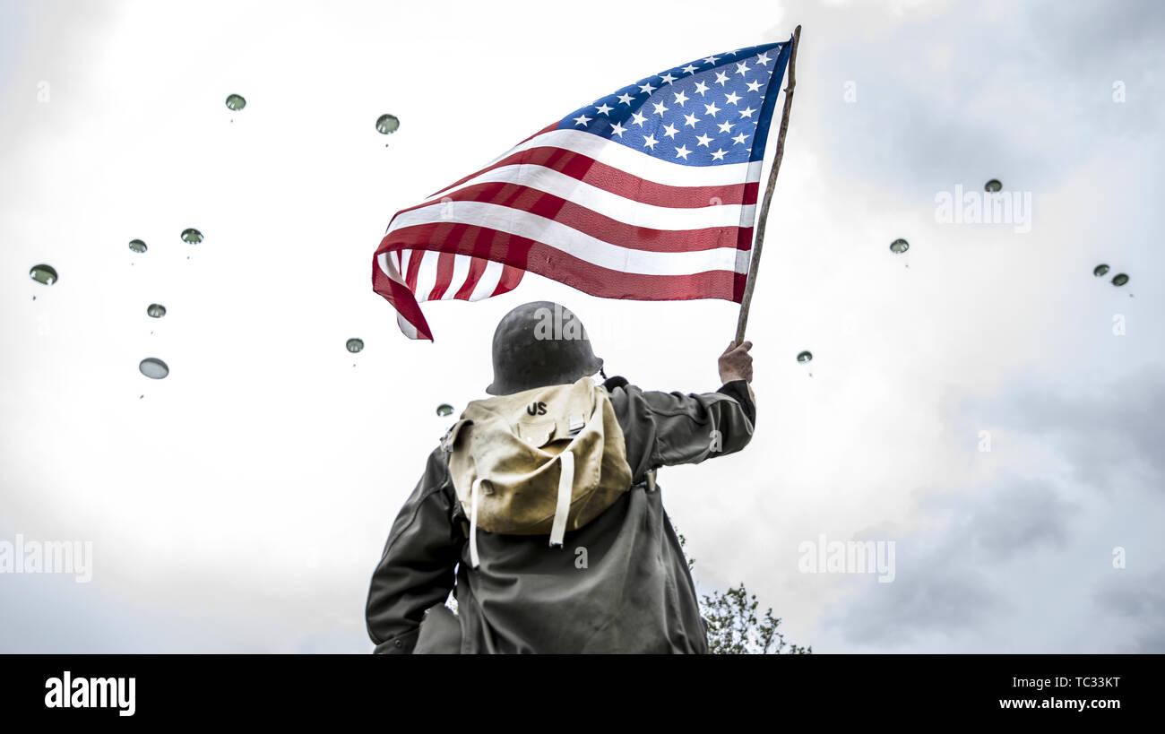 Carentan, France. 5 juin, 2019. Un homme habillé comme un fantassin américain oreille WWII vagues le drapeau américain comme parachutistes sont vus dans le ciel, lors d'un saut commémoratif le long de la 'Purple Heart Lane', Carentan, France le 5 juin 2019. Credit: Omer Messinger/ZUMA/Alamy Fil Live News Photo Stock