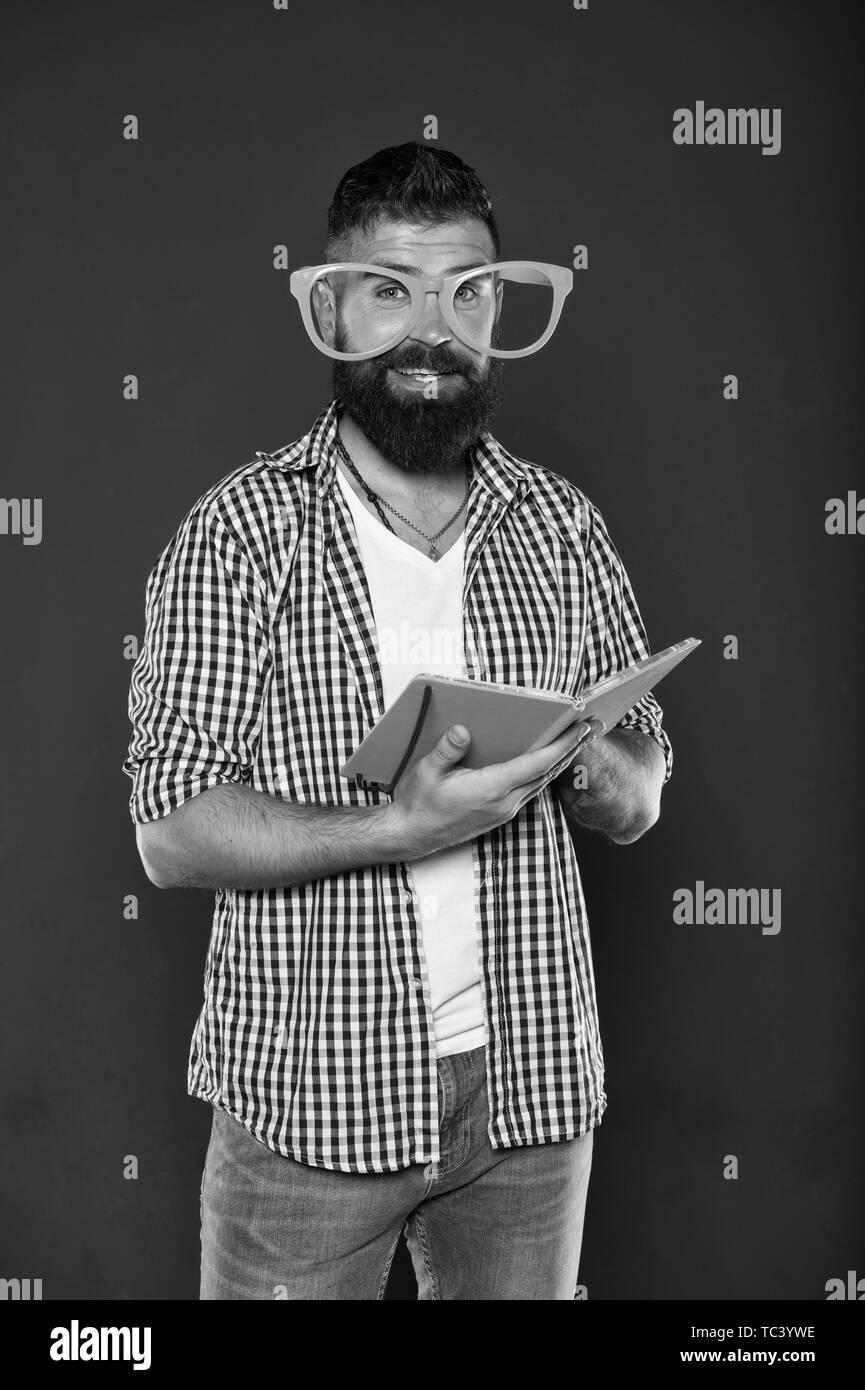 Cours d'éducation des adultes. Auto éducation concept. Club littéraire. Lecture du livre comme passe-temps. Étude est amusant. Homme barbu hippie lunettes drôles tenir le bloc-notes ou livre. Lisez ce livre. Comique et l'humour de bon sens. Photo Stock