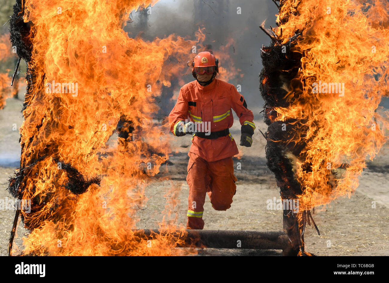 Hohhot, Chine, région autonome de Mongolie intérieure. 5 juin, 2019. Un pompier nouvellement recrutés traverse un mur de feu au cours d'une formation à Hohhot, Chine du nord, région autonome de Mongolie intérieure, le 5 juin 2019. Plus de 1 100 pompiers volontaires recrutés socialement reçoivent une formation de six mois à Hohhot. Credit: Peng Yuan/Xinhua/Alamy Live News Photo Stock