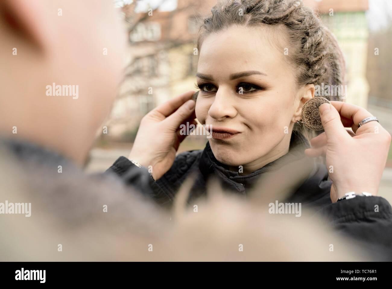 L'homme spirituel de boucles d'alternative holding femme drôle, à l'extérieur, en Cottbus, Brandebourg, Allemagne Photo Stock