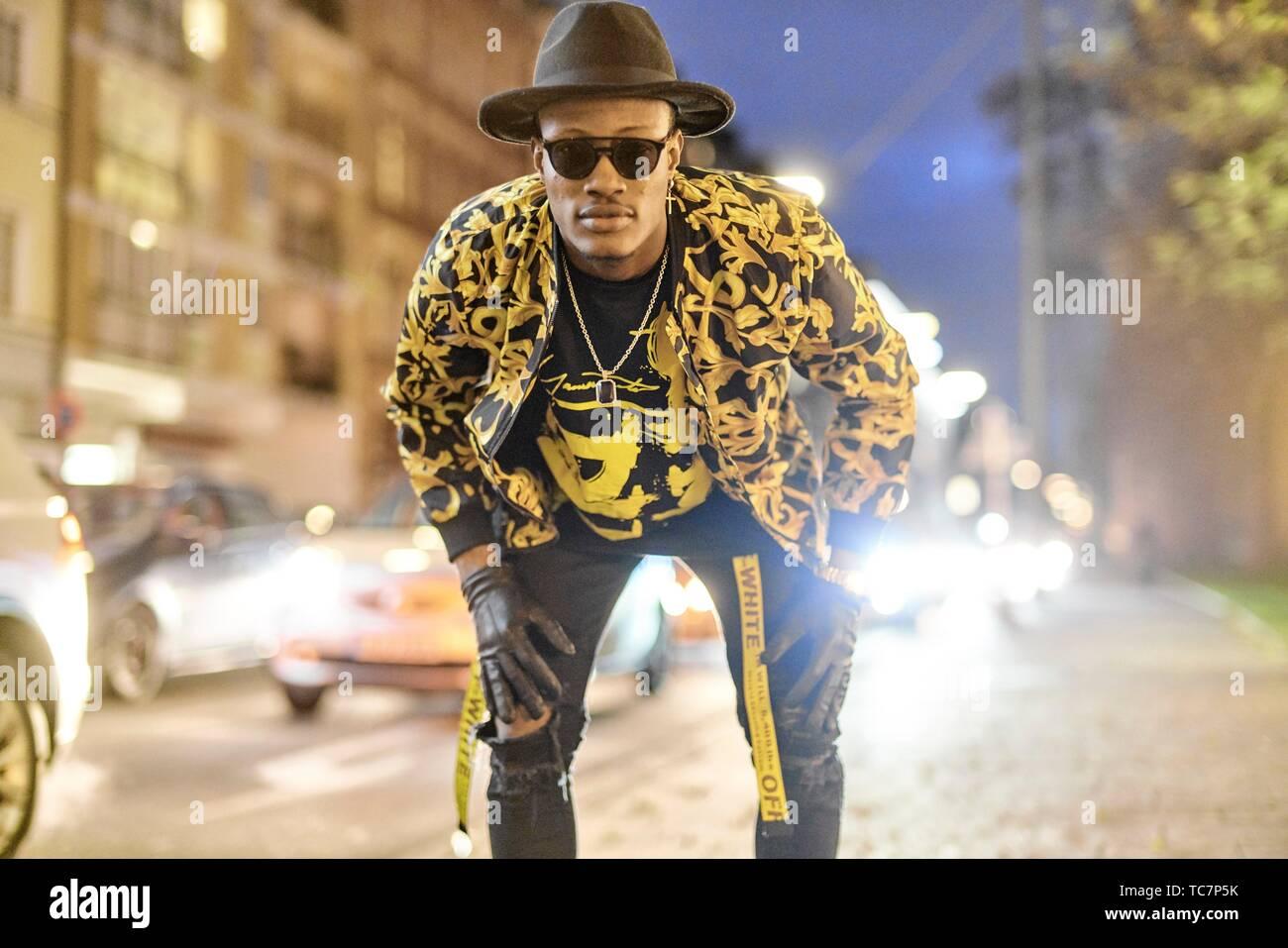 Homme fantaisie au city street at night, voiture, attitude prétentieuse, Cool attitude, tenue élégante, à Munich, en Allemagne. Photo Stock