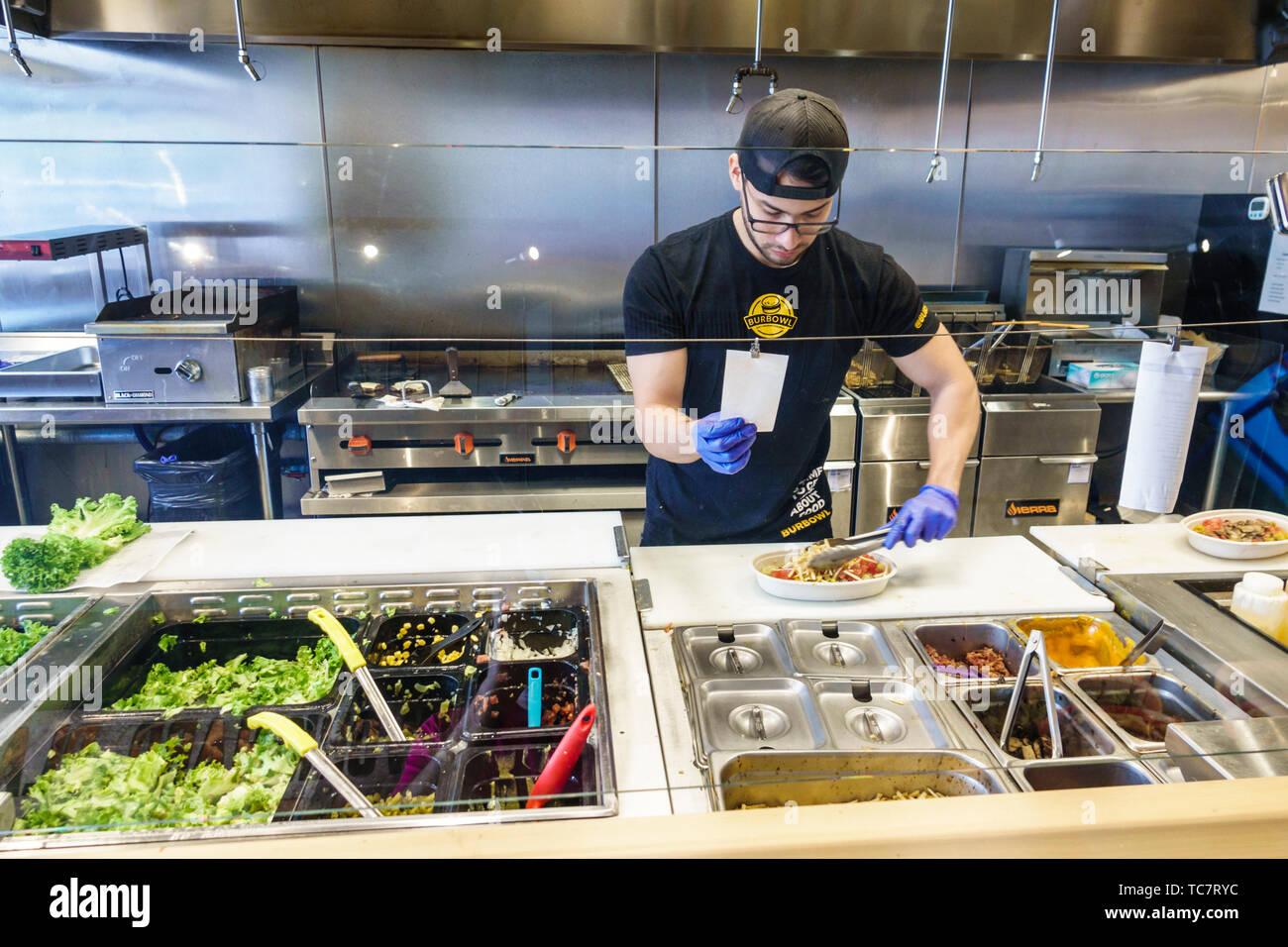 BurBowl Doral Miami Florida restaurant au sein du personnel de l'employé de la préparation des aliments hispaniques travailleur homme salade ordre station bien à usage unique hygiène sécurité glo Photo Stock