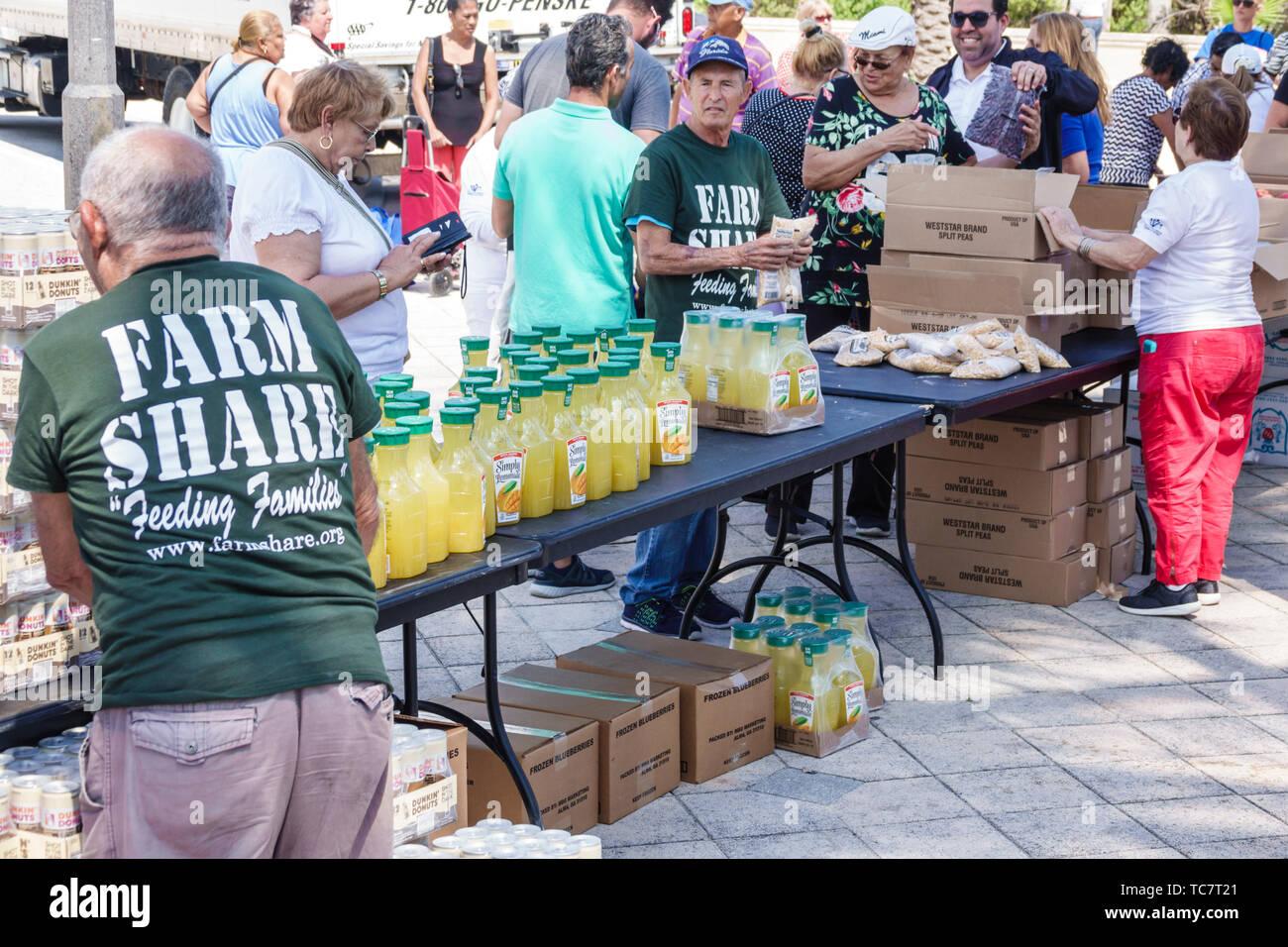 Floride Miami Beach North Beach Ocean Terrace Farm partager la nourriture, donner la distribution gratuite des bénévoles à faible revenu dans le besoin homme femme portrait Photo Stock