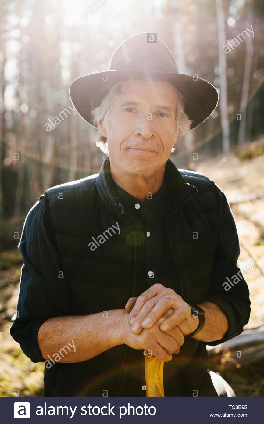 Portrait confiant mature man hiking in sunny woods Photo Stock