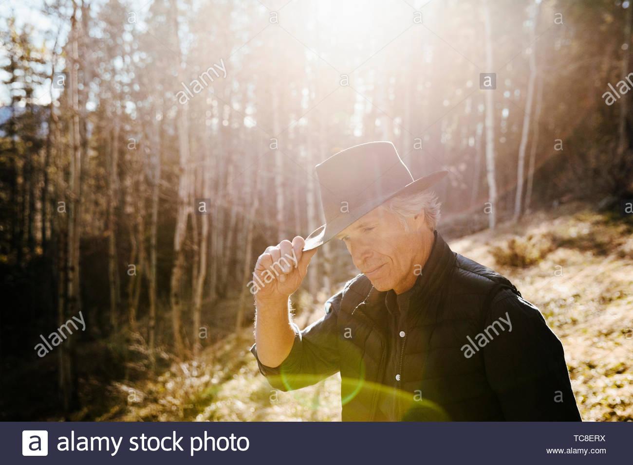 Mature man in hat randonnées à sunny woods Photo Stock