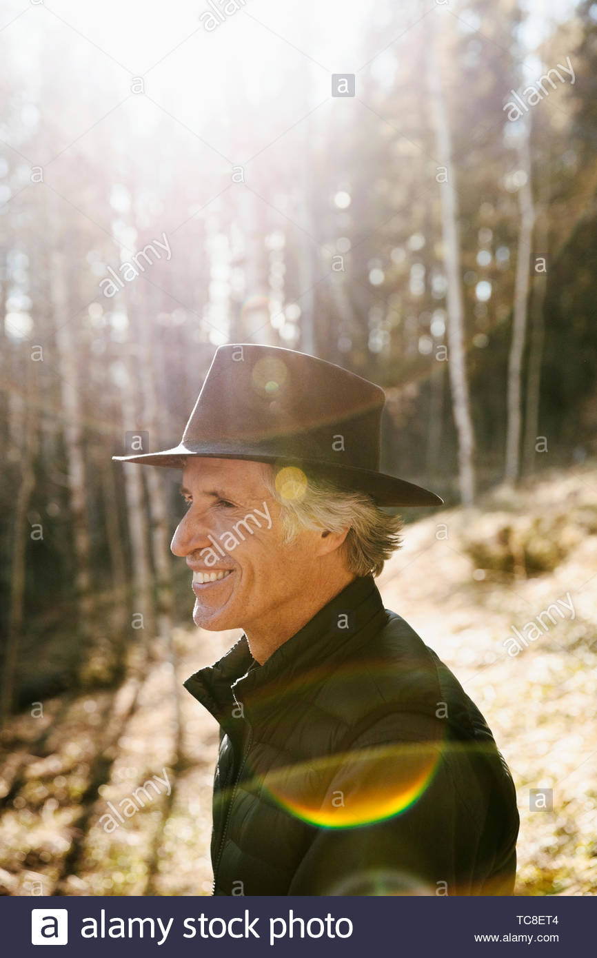 Smiling Young man with hat randonnées à sunny woods Photo Stock