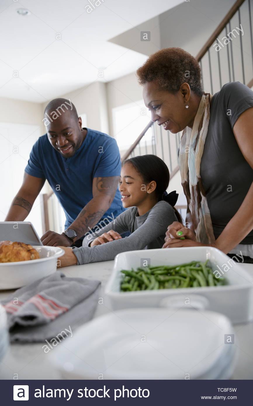 Multi-generation family with digital tablet à préparer le dîner dans la cuisine Photo Stock