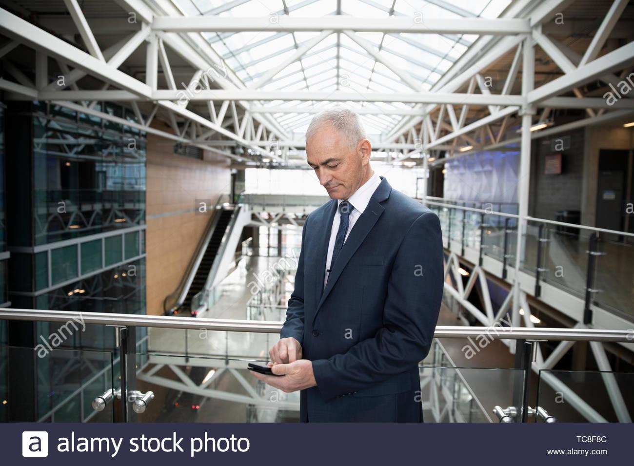 Businessman using smart phone sur atrium bureau balcon Photo Stock