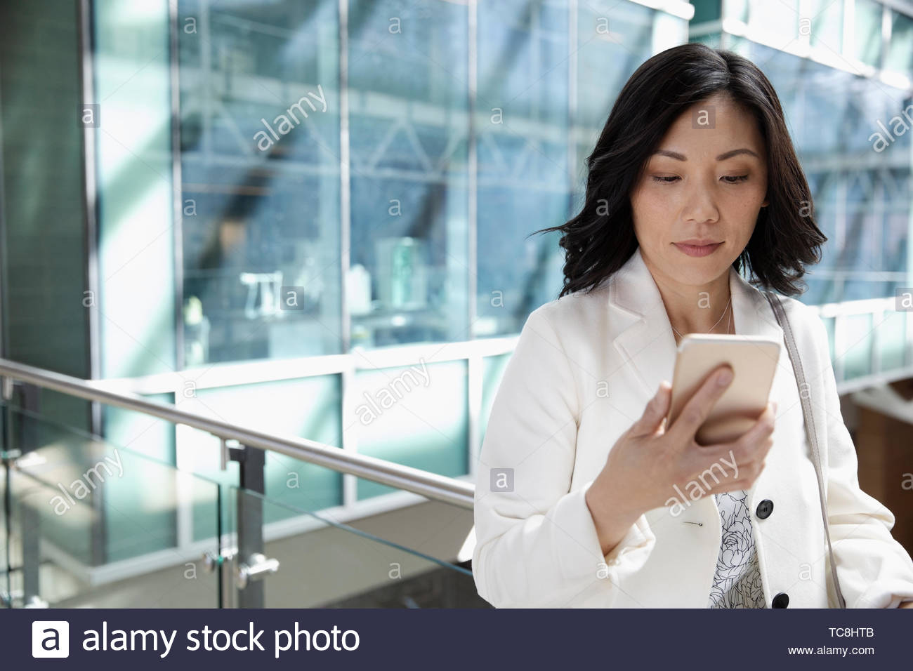 Young businesswoman using smart phone sur balcon bureau Photo Stock