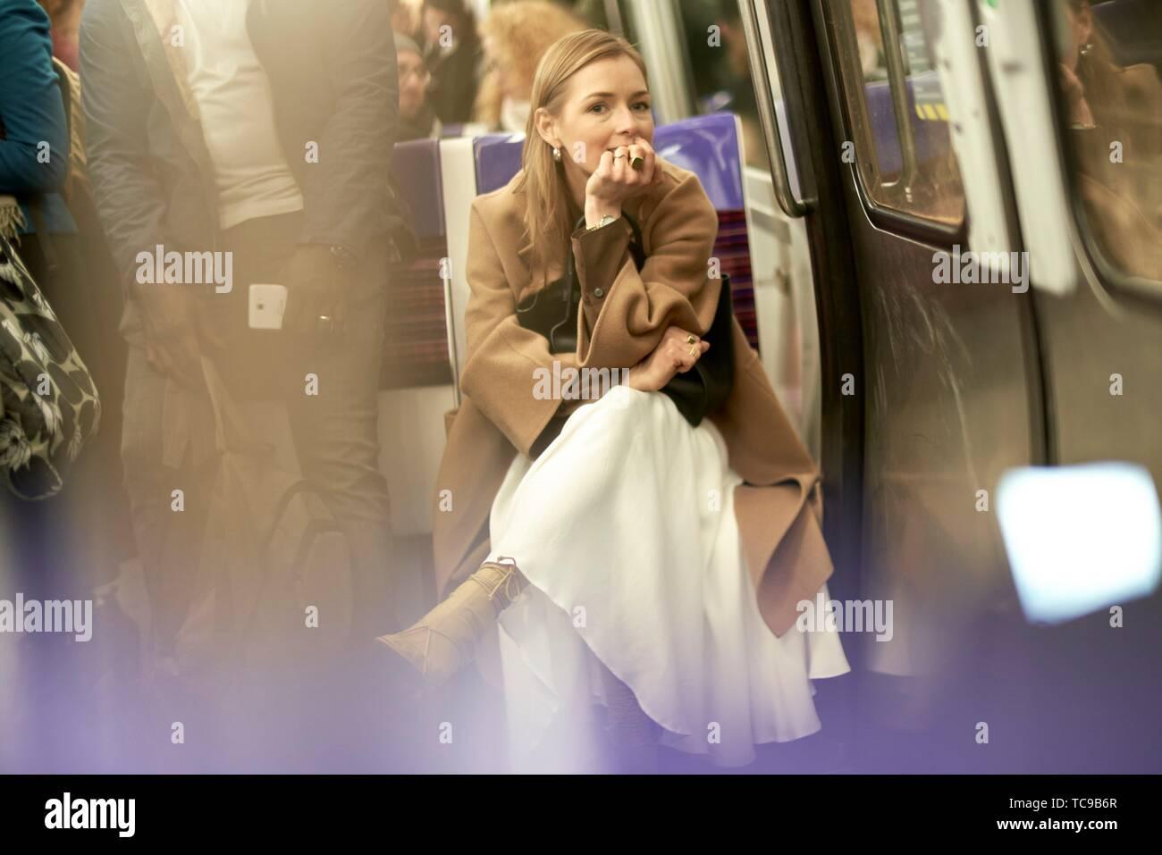 Blogger à la mode femme assise dans le métro, en utilisant les transports publics, au cours de la semaine de la mode, ville de Paris, France Banque D'Images