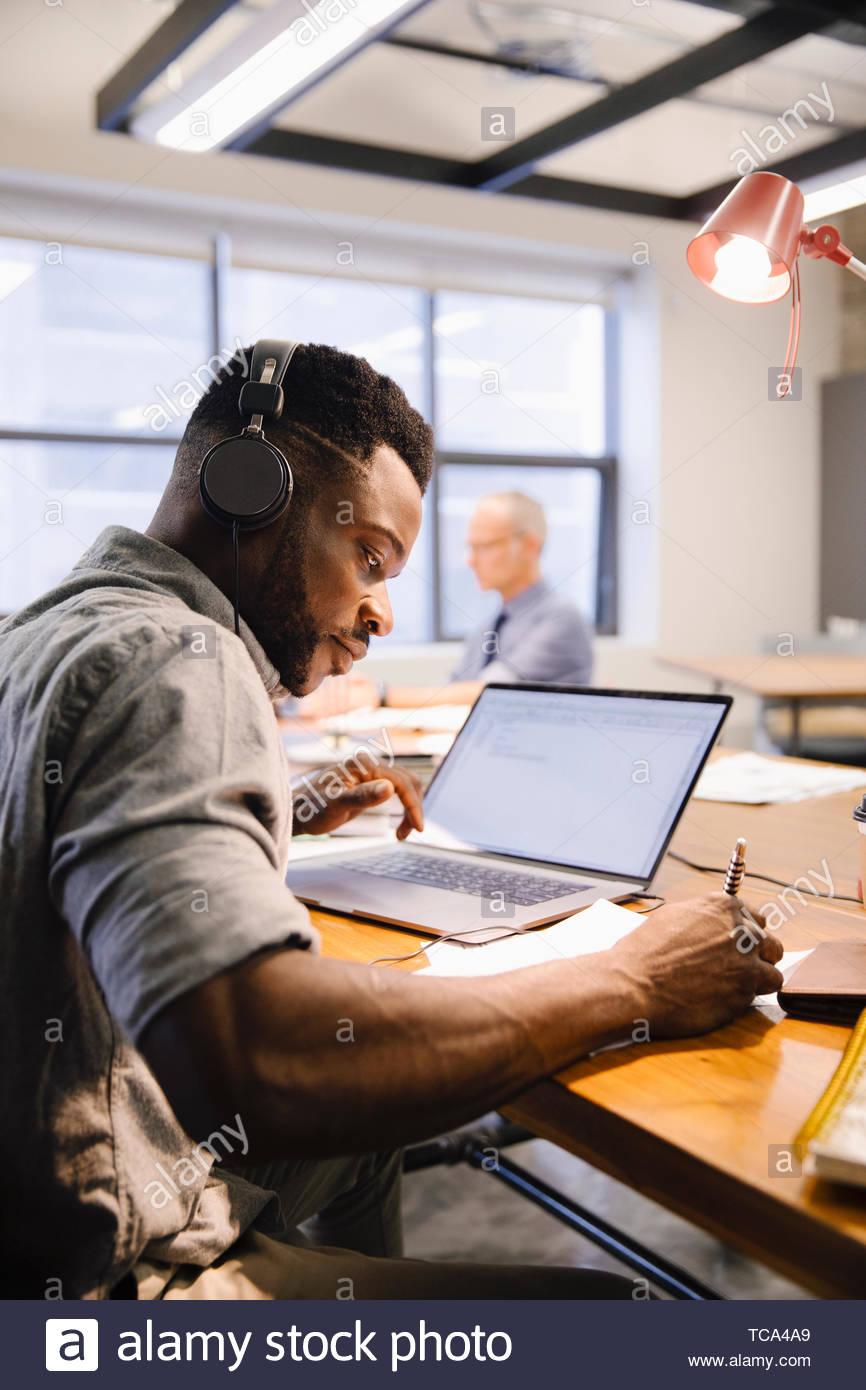 L'accent creative businessman with headphones working at laptop en espace de coworking Photo Stock