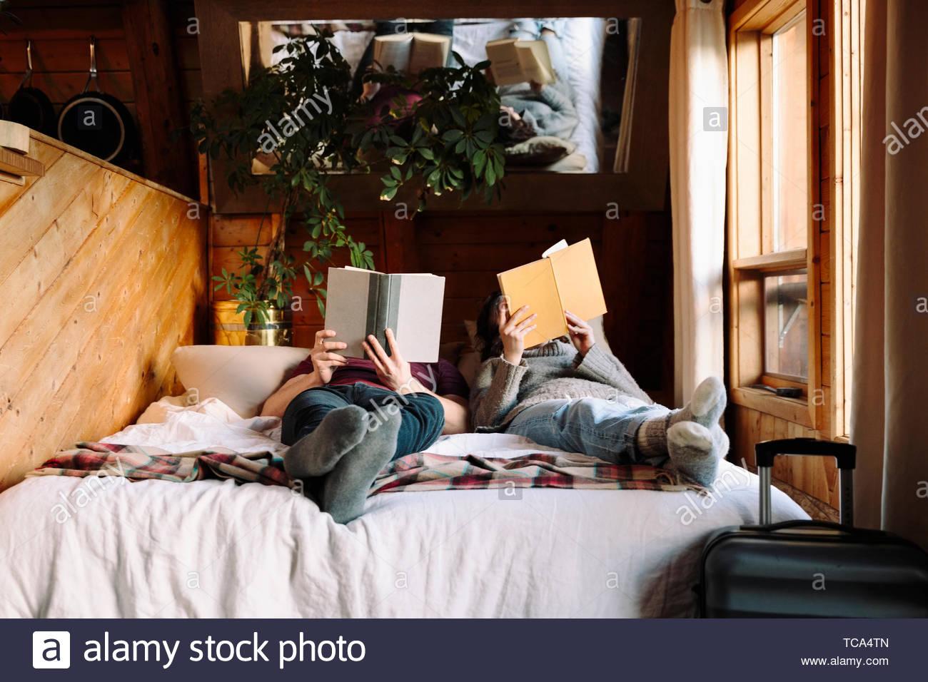 Couple, la lecture de livres sur lit de cabine Photo Stock
