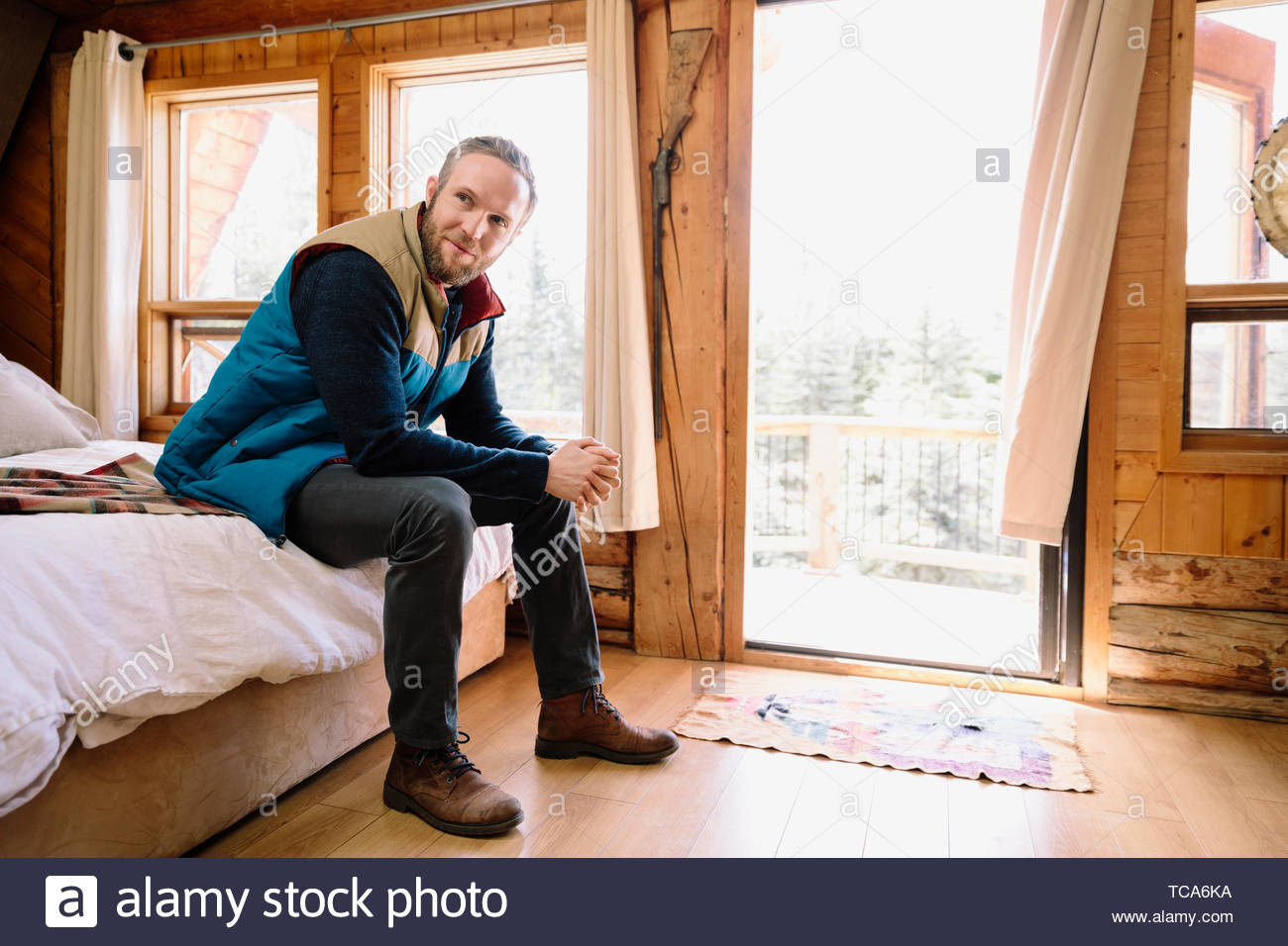 Portrait of smiling man relaxing on bed cabin Banque D'Images